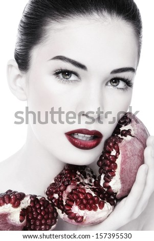 Duotone portrait of young beautiful woman with pomegranates in her hands, on white background - stock photo