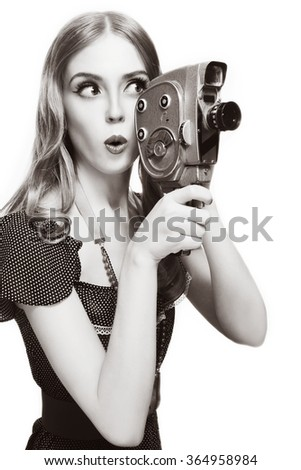 Duotone shot of young beautiful curious girl with vintage camera over white background, copy space - stock photo