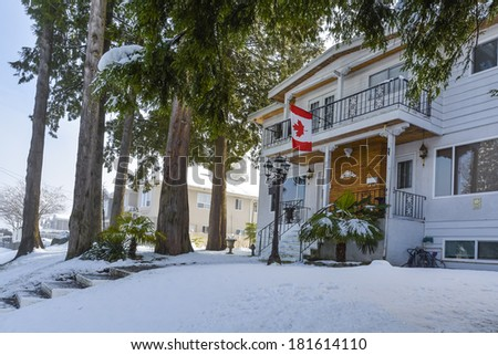 Duplex house on snowy day in winter. Duplex house with Canadian flag in front in snow. - stock photo