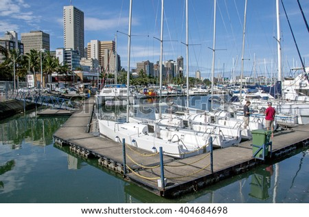 DURBAN, SOUTH AFRICA - APRIL,8, 2016: Two unknown men on wooden walkway and yachts moored in harbor at Wilsons Wharf against city skyline in Durban South Africa