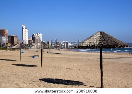 DURBAN, SOUTH AFRICA - DECEMBER 18, 2014: Three wooden sunshades and many unknown people on Addington Beach in Durban, South Africa