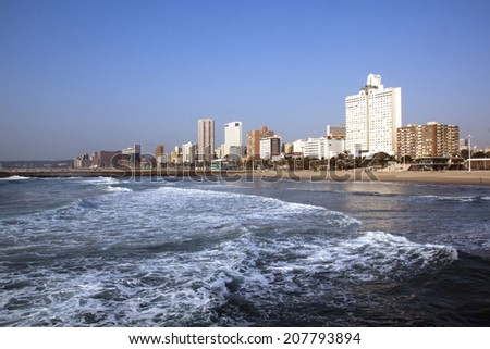 DURBAN, SOUTH AFRICA - JULY 23, 2014: Early morning view of ocean and empty beach against city skyline in Durban, South Africa