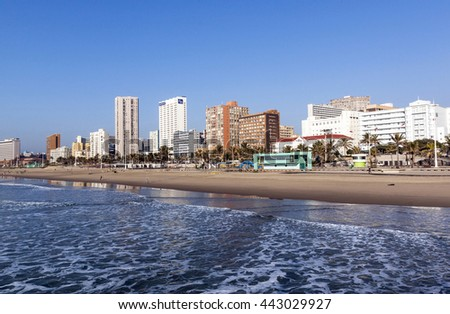 DURBAN, SOUTH AFRICA - JUNE 24, 2016: Early morning landscape of calm ocean empty beach  against Golden Mile city skyline in Durban, South Africa