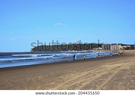 DURBAN, SOUTH AFRICA - JUNE 16, 2014: Many unknown people fish and walk along Addington beach in Durban, South Africa