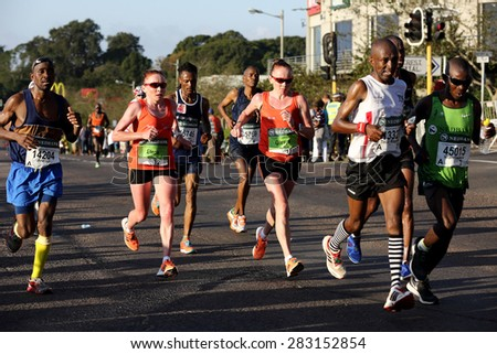 DURBAN, SOUTH AFRICA â?? MAY 31: Russian twins trail race leader Caroline Wostmann as they run through Hillcrest in the 2015 Comrades marathon Up run in Kwa Zulu Natal, South Africa on May 31, 2015.  - stock photo