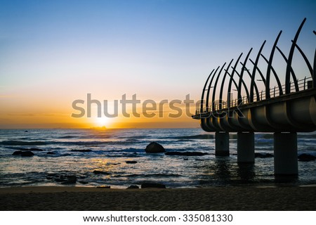 Durban Umhlanga pier in south africa in the golden morning sunrise with ships on the horizon  - stock photo