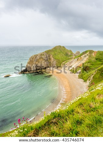 Durdle door is natural limestone arch at coastline, with surrounding cliff and coastline under rain cloudy sky,  located at Dorset in England