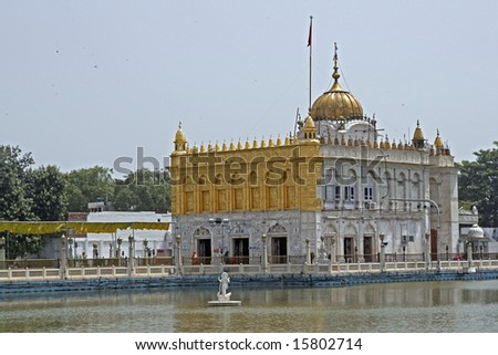 Durgiana Hindu Temple. White marble building with gold dome set in artificial lake. Amritsar, Punjab, India