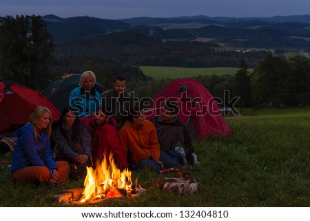 During night camping friends setting fire beside tents - stock photo