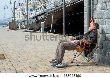 During the lunch break, a man falls asleep on a chair easily. - stock photo