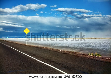Dusk in Bonneville Salt Flats, Utah with street sign alongside freeway road with dramatic clouds in sky landscape - stock photo