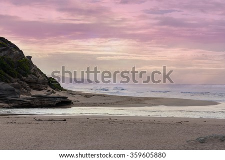 dusk over the ocean waves river mouth and headland, painted pink in the evening sky - stock photo