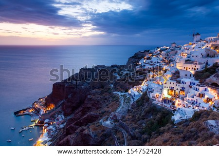 Dusk overlooking Amoudi Bay from Oia Santorini Greece Europe - stock photo