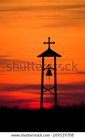 Dusk scene of Christian bell and cross silhouette on meadow - stock photo