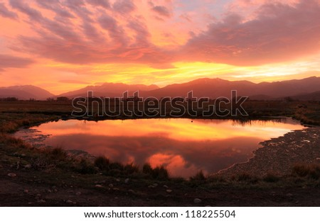 Dusk sky reflecting in a pond in the Utah mountains, USA. - stock photo
