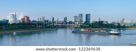DUSSELDORF, GERMANY - AUGUST 11: Container ship on august 11, 2012 in Dusseldorf, Germany. As harbor lost its importance, nowadays the area itself contains some spectacular post-modern architecture. - stock photo