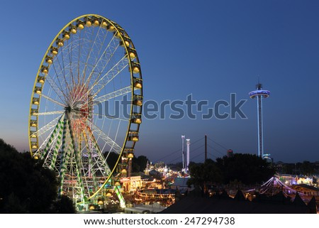 DUSSELDORF, GERMANY - JULY 21, 2013: Bridge view on a fair with giant ferris wheel and amusement rides on  July 21, 2013 in Dusseldorf. - stock photo