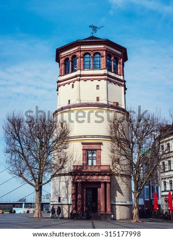 DUSSELDORF, GERMANY - MARCH 19, 2014: People in front of Schlossturm in Altstadt in the sunny spring day. Famous landmark in the city