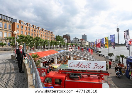 DUSSELDORF, GERMANY - MAY 26: Tourists visit  Rhine river and the tower of St Lambertus church on May 26, 2011 in Dusseldorf, Germany. The Embankment of Rhine river in Dusseldorf historic center