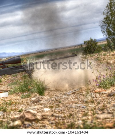 Dust and smoke rising from a snipers rifle after a shot