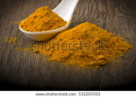 dust of ground turmeric on the wood background