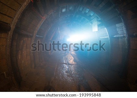 dusted tunnel in coal mine, silhouette of miner with flashlight - stock photo