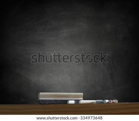 Duster and chalk in front of blackboard - stock photo