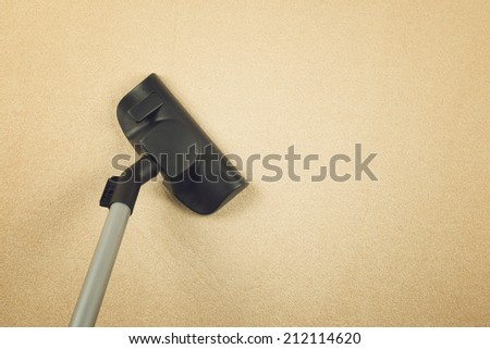 Dusting the carpet with brand new Vacuum Cleaner as Housework and home hygiene conceptual image with copy space. - stock photo