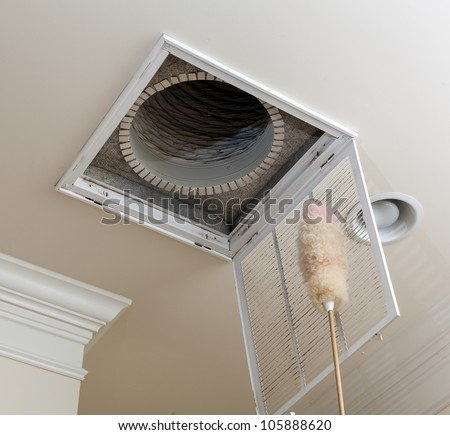 Dusting the vent for air conditioning filter in ceiling of modern home - stock photo