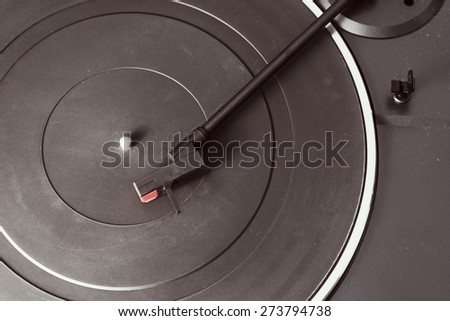 Dusty an old black domestic phono turntable with scratches.