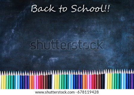 Dusty blank school chalkboard or blackboard and colored pencils with Back to School text and copy space.