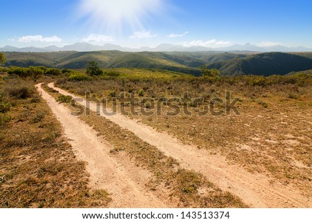 dusty country road in farmland fields and mountain landscape - stock photo
