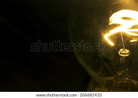 Dusty Incandescent tungsten light bulb on a dark background. - stock photo