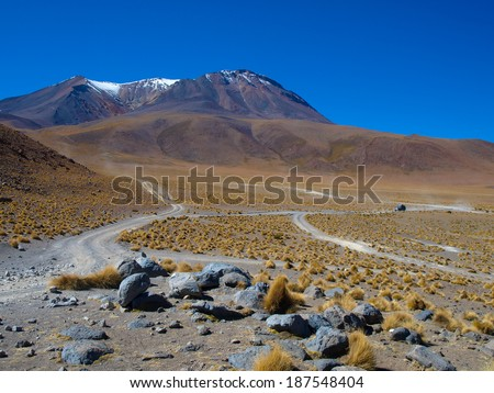 Dusty roads of altiplano area in southern Bolivia. High volcano with snowy peaks on the horizon. - stock photo
