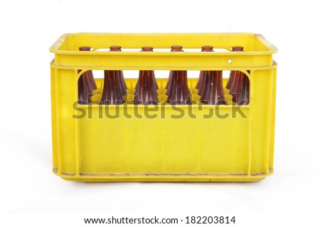 Dusty vintage yellow beer crate with empty brown beer bottles on white background - stock photo