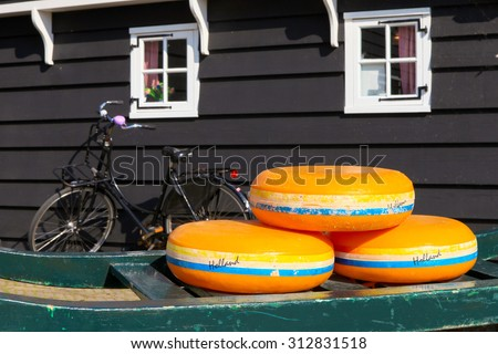 Dutch Cheese wheels on a green cart with farm house in the background - stock photo