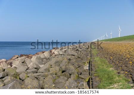 Dutch dike along the sea with wind turbines - stock photo