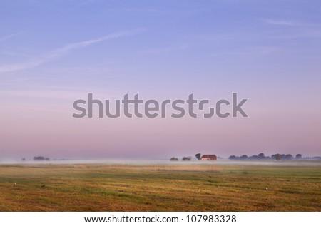 Dutch farm on horizon during early sunrise - stock photo