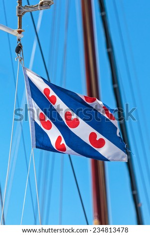 Dutch flag of the province Friesland hanging on a rope of a sailing ship - stock photo
