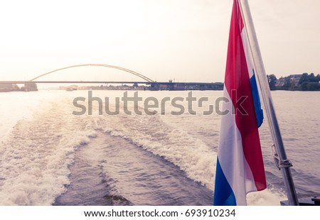 Dutch flag on rear of boat sailing on Beneden-Merwede with a bridge in the distance, Netherlands