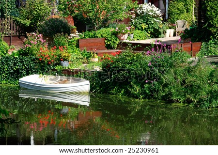 Dutch flower garden with boat on a canal (Amsterdam) - stock photo