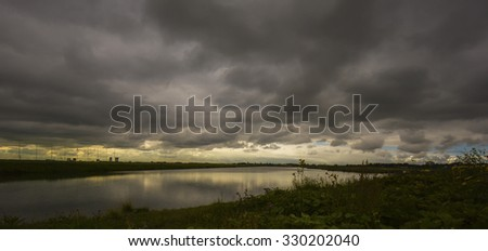 Dutch landscape at dawn with a dark cloudy sky above the Willem-Alexanderbaan in Zevenhuizen (the Netherlands). On the left the suburb Nesselande and the flag poles of the rowing course