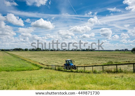 Dutch landscape with a tractor and beautiful clouds