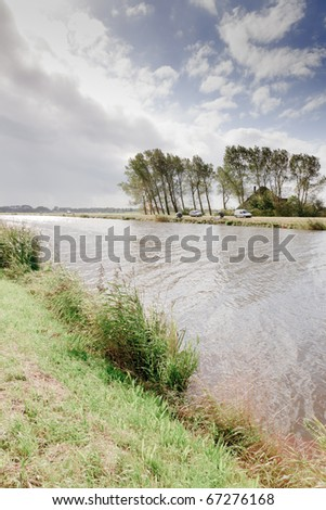Dutch landscape with canal under cloudy sky