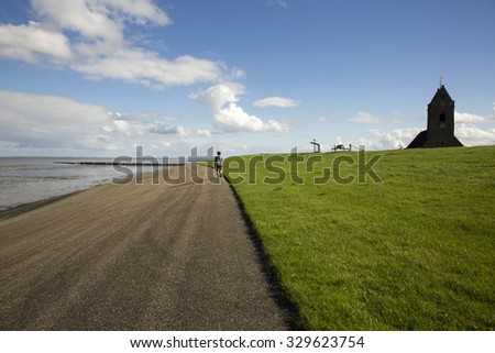 Dutch landscape with view on the dam and  old medieval church of Wierum, Friesland, The Netherlands - stock photo