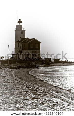Dutch Lighthouse in the winter picture made against the sunlight - stock photo
