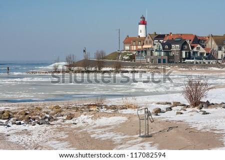 Dutch lighthouse in wintertime near a frozen sea - stock photo