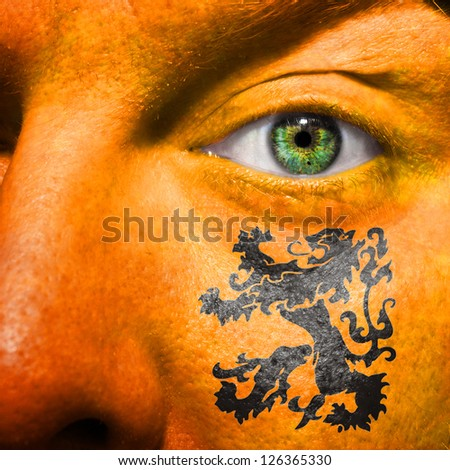 Dutch Lion painted on orange face with green eye - stock photo