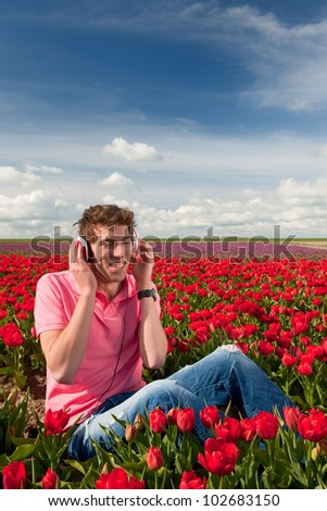 Dutch man sitting in flower fields listeing to cool music - stock photo