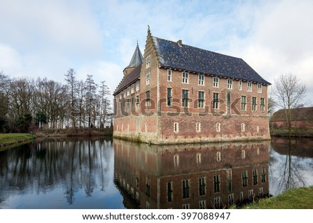 Dutch medieval castle built in 1474, reflected in the mirror smooth water surface of the moat on a beautiful day at the beginning of the spring season.